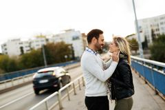Happy young couple hugging and kissing on bridge Royalty Free Stock Images