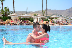 Happy young couple hugging and kissing in the pool. Happy young couple on summer vacation Royalty Free Stock Photography