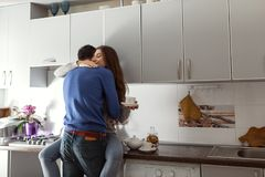 Happy young couple hugging on kitchen. Woman sitting on table. stock image