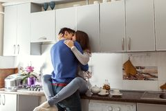 Happy young couple hugging on kitchen. Woman sitting on table. royalty free stock photos