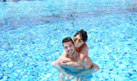 Happy young couple hugging in the pool. Happy young couple on summer vacation Stock Photos