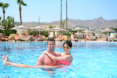 Happy young couple hugging in the pool. Happy young couple on summer vacation Stock Photography