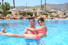 Happy young couple hugging in the pool. Happy young couple on summer vacation Royalty Free Stock Photos