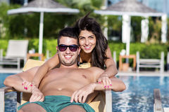 Happy young couple hugging and relaxing on the pool Royalty Free Stock Photos