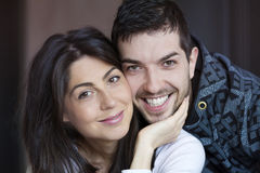 Happy young couple hugging and smiling indoor Stock Images