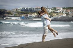 Young woman in white dress watching sea waves on Sao Miguel beach with black voncanic sand, AzoresHappy young couple on windy beac royalty free stock photo