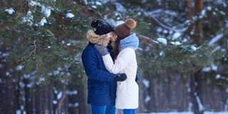 Happy young couple hugs in winter snowy woods stock photos