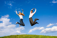 Happy Young Couple jumping. Happy Young Couple - team is jumping above a green meadow. Against the backdrop of blue sky Stock Image