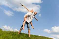 Happy Young Couple jumping above green meadow. Happy Young Couple - jumping above a green meadow. Against the backdrop of blue sky Stock Image