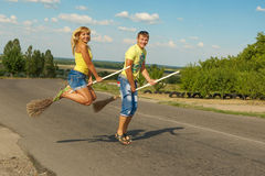 Happy young couple jumping with a broom Royalty Free Stock Photo