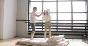 Happy young couple are jumping and hugging in bed holding hands in their new flat. Relationship concept. stock video
