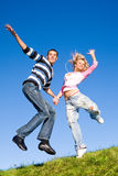 Happy young couple jumping in sky royalty free stock photo