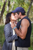 Happy young couple kissing. Young multi cultural couple kissing in fall forest Royalty Free Stock Photos