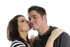 Happy young couple kissing. Portrait of young woman kissing happy man on cheek, white background Stock Photography