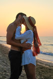 Happy young couple kissing at the beach at dusk Royalty Free Stock Photography