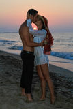 Happy young couple kissing at the beach at dusk Royalty Free Stock Photo