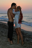 Happy young couple kissing at the beach at dusk Royalty Free Stock Image