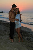 Happy young couple kissing at the beach at dusk Stock Photography