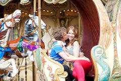 Happy young couple kissing in an equipage of me. Happy young couple kissing in an equipage of vintage Parisian merry-go-round royalty free stock image