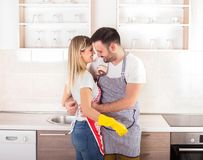 Young couple hugging after housework. Happy young couple kissing and hugging in kitchen after housework is done Royalty Free Stock Images
