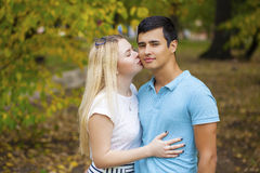 Happy young couple kissing outdoor in the autumn park Royalty Free Stock Photo