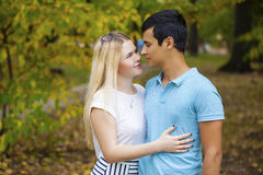 Happy young couple kissing outdoor in the autumn park Stock Image