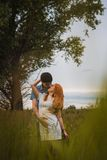 Happy young  couple kissing on a ripe field Royalty Free Stock Photography