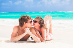 Happy young couple kissing on a tropical beach in Stock Images