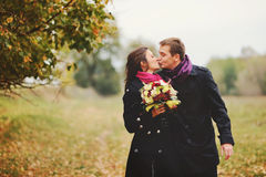 Happy young couple kissing. Walking in garden Royalty Free Stock Photos