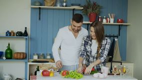 Happy young couple in the kitchen. Attractive dancing man cooking while his girfriend come and help him in the morning. At home stock video