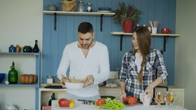 Happy young couple in the kitchen. Attractive dancing man cooking while his girfriend help him in the morning. At home stock video footage