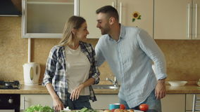 Happy young couple in the kitchen. Attractive woman cooking breakfast and cuff her boyfriend who want to taste food
