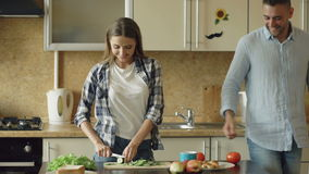 Happy young couple in the kitchen. Attractive woman cooking breakfast and cuff her boyfriend who want to taste food stock video footage