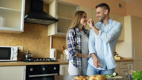 Happy young couple in the kitchen. Handsome man meet and feed his girlfriend early morning. Happy young couple in the kitchen. Handsome men meet and feed his Stock Photos