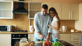 Happy young couple in the kitchen. Handsome man meet his girlfriend early morning. Happy young couple in the kitchen. Handsome men meet his girlfriend early Royalty Free Stock Image
