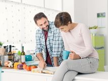 Couple searching recipes on the cookbook stock photo