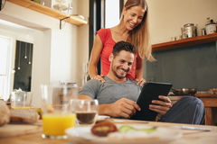 Happy young couple in kitchen using tablet pc Royalty Free Stock Photo