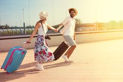 Happy couple arrived at the holiday destination. Happy young couple landed at the airport, arrived at the destination of vacation stock photo
