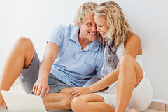 Happy young couple with laptop. Smiling Royalty Free Stock Photos