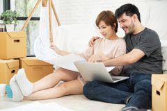 Young couple planning their new house. Happy young couple with laptop and blueprints planning their new moving house. Smiling each other royalty free stock photos