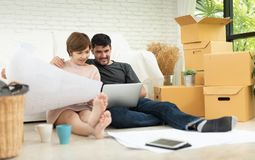 Young couple planning their new house. Happy young couple with laptop and blueprints planning their new moving house. Smiling each other stock photos