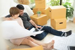 Young couple planning their new house. Happy young couple with laptop and blueprints planning their new moving house. Smiling each other royalty free stock photo