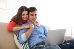 Happy young couple with laptop. At home Royalty Free Stock Photos
