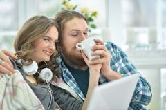 Happy young couple with laptop. Portrait of happy young couple with laptop at home Stock Photos