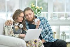 Happy young couple with laptop. Portrait of happy young couple with laptop at home Stock Image