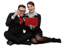 Happy Young Couple on Laptops. Happy young business couple looking at the notebook while sitting against a white background Stock Image