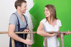 Happy young couple laughing as they redecorate royalty free stock photos