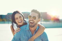 Happy young couple laughing in piggyback pose at oudoors stock photo