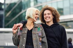Happy young couple laughing in urban background. Happy couple laughing in urban background. Young woman and man enjoying each other stock images