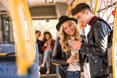 Happy young couple in leather jackets using smartphone in public. Transport Royalty Free Stock Photo